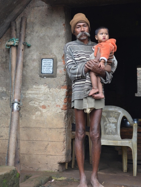 Balaraju Raasa in front of his family's unfinished hut, carrying his granddaughter Ramya.