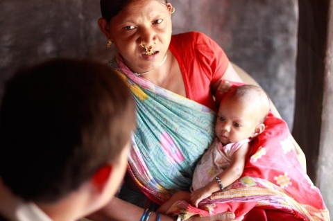 A visiting doctor examines a feverish infant at a mobile health clinic in Koraput, a disadvantaged district of India with rampant malaria and a severe shortage of care.