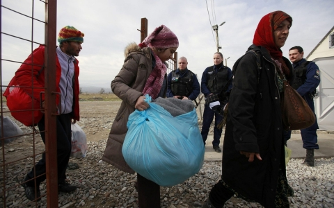 Hungarian police officers control the arrival of refugees crossing the border from Greece, at the entrance of the transit center near the southern Macedonia's town of Gevgelija, on Jan. 11, 2016.