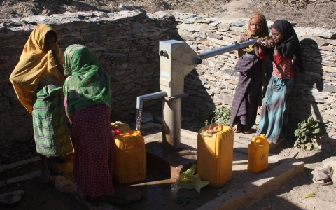 A foreign-funded watering hole where young girls work together collecting water
