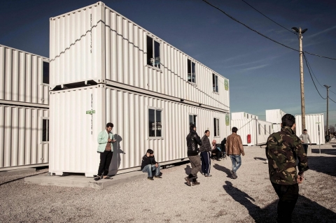 Migrants walk past housing containers in the refugee camp in the port town of Calais, in northern France, on Feb. 16, 2016.