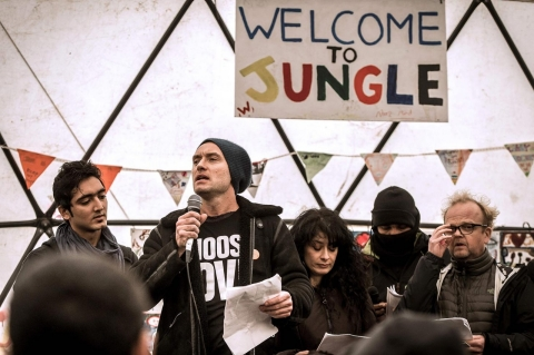 British actor Jude Law (center) speaks during a visit to the Jungle migrant camp in Calais on Feb. 21, 2016.