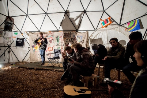 Migrants listen to a guitarist performing in a makeshift theater on Nov. 25, 2015, in the Jungle migrant camp in Calais, northern France.