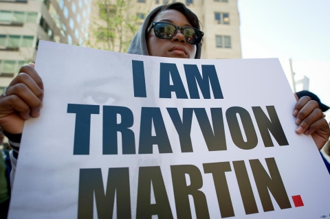 "A protester carries a poster reading"" I am Trayvon Martin"" during a rally in downtown Washington DC on March 28, 2012. Protesters gathered outside the American Legislative Exchange Council's (ALEC) headquarters to protest against the laws protecting the ""justifiable homicide"" passed in more than half of the US states."