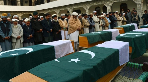 Pakistan security officials attend the funeral ceremony of police officials killed in twin bomb explosions near the Afghan border with Pakistan. The men from the tribal Khasardar Force were guarding polio vaccinators when they were killed, officials said.