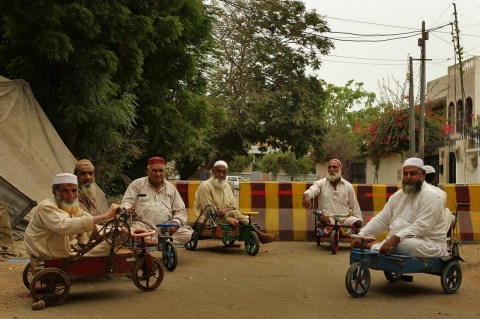 A group of men with polio sit in their bicycle carts in the streets of Karachi on Aug. 10, 2011.