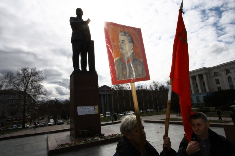 A supporter of Crimea's joining Russia holds a poster of Stalin in front of the statue of Lenin in Simferopol's Lenin Square.