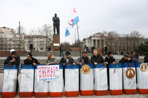 "Members of Crimea's newly formed pro-Russia ""self-defense forces"" guard Lenin Square, Simferopol."