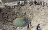 Iraqis survey a crater left after a US air strike in the flashpoint town of Fallujah, west of Baghdad on September 02, 2004. Twenty Iraqis were killed and six wounded in a US air strike overnight