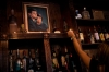 A bartender places a candle near a portrait of John F. Kennedy and Jacqueline Kennedy in the Kennedy Room bar in Dallas, Texas.
