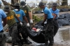 Members of the Philippine National Police transport a body bag with a typhoon victim in Tacloban.