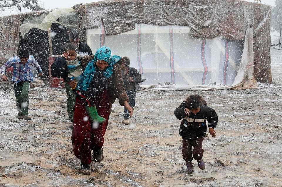 Syrian woman walks wit her sons under the snow