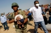 Turkish soldier carries Syrian refugee baby