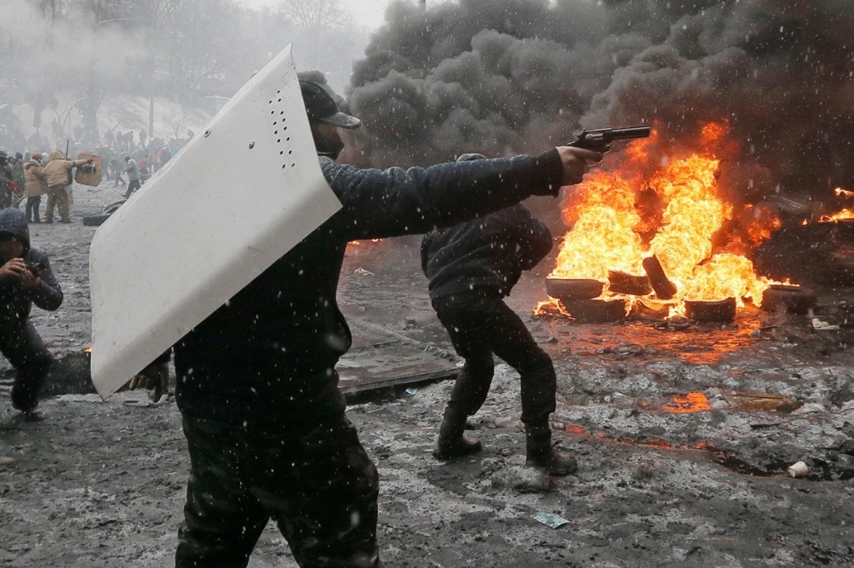 A protester points a handgun during a clash with police in central Kiev, Jan. 22. Efrem Lukatsky/AP