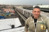Andrew Coté stands in front of the train a rooftop where he keeps beehives in Bushwick, Brooklyn.
