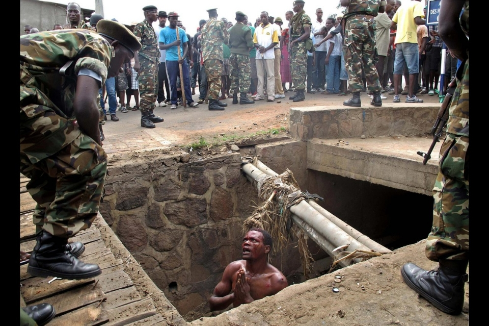 Man begs soldiers for help from a drain where he had hid to escape