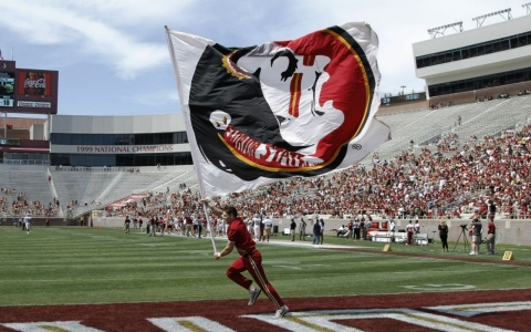 A Florida State cheerleader carries a flag during a spring football game. The Florida State team is among the NCAA programs that have had had a player accused of or charged with a sex crime this year.