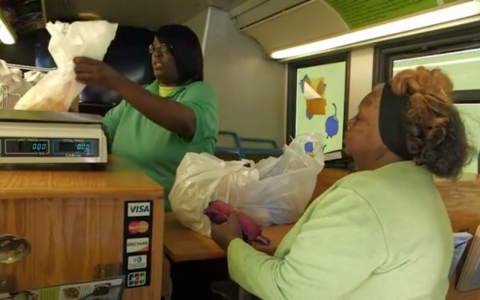 Betty Isom, right, buys bags full of fresh fruits and vegetables from the Green Machine. She hopes the modified bus will help address the needs of a community that has a 34-percent obesity rate among its adults.