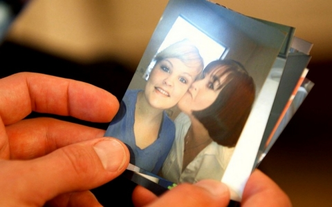 Lori Clarine holds a picture of herself (right) with her daughter, Regan.