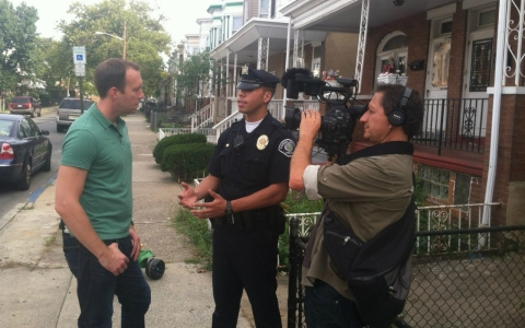 Adam May speaks with a police officer in Camden, N.J.