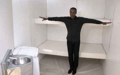Correspondent Michael Okwu stands inside a replica cell at an exhibit hosted by the Prison Hunger Strike Solidarity Coalition.