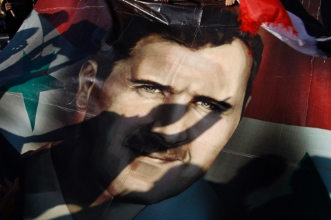 Shadows of Syrians are reflected on a giant poster showing President Bashar Assad, during a supporting rally in Damascus, Syria, Friday, Dec. 16, 2011. (AP Photo/Muzaffar Salman)