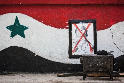 This Sunday, Dec. 16, 2012 photo, shows a damaged portrait of former Syrian President Hafez Assad at the entrance of a military academy besieged by rebels during heavy clashes with government forces north of Aleppo, Syria. (AP Photo/Narciso Contreras)