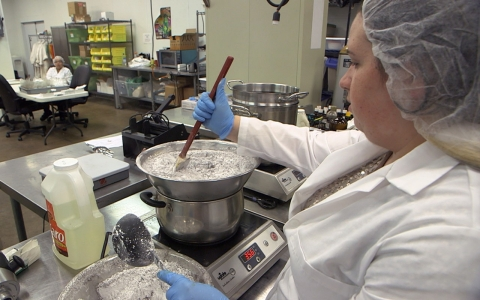 An employee makes a chocolate candy that will eventually look like a Tootsie Roll. It will sell for approximately $8.