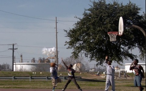 Kids play basketball near an oil refinery in Port Arthur, Texas.