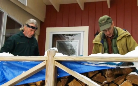 Larry Davis and Dwight Schenk, 67, stack wood for Ann Pliska.
