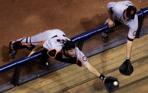 Mike Matheny, left, then with the San Francisco Giants, dives over the railing to catch a ball.