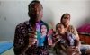 "Md. Khwaja Miah, 47, holds a picture of his daughter, Khairunnahar Munni, 20, who ""rushed to work after her supervisor called and ordered"" her to come in."