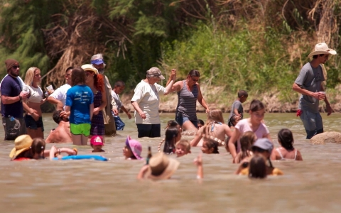 "Kids and adults play in the Rio Grande River during the ""fiesta protesta."""