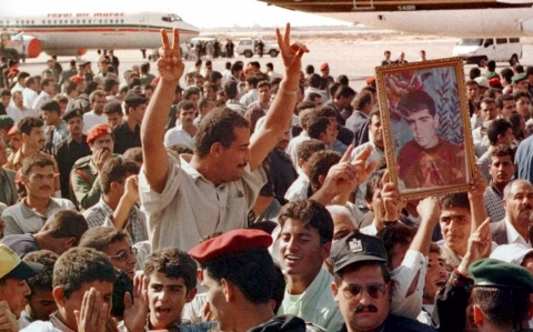 "A Palestinian man gives the ""victory"" sign as he celebrates with others the opening of the Gaza International airport in Dahanieh Tuesday Nov. 24, 1998."