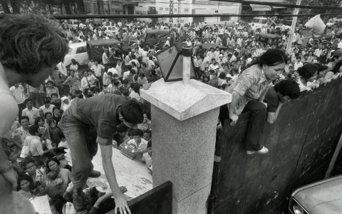 South Vietnamese civilians try to climb the wall of the embassy