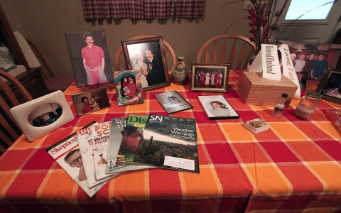 Cathy Senderak's kitchen table memorial for her husband Joseph includes his collections of fossils, science magazines and jars of sand from around the world.