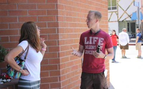 The Rev. James Conrad, right, engages with a passerby in Los Angeles about the anti-abortion movement.