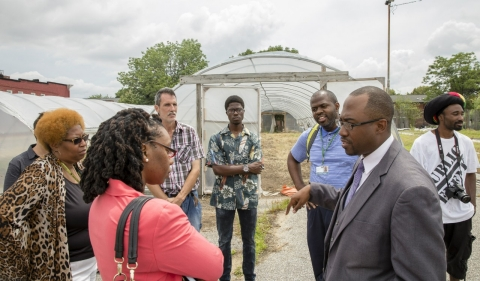 Rev. Dr. Heber Brown speaks to local residents and leaders outside one of the sites for the Black Dirt Farm.