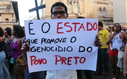 "Tens of thousands of people participated in Reaja's annual international march against the genocide of black people. This protester holds up a sign that reads in Portuguese: ""The white media assists the killing of black people."""