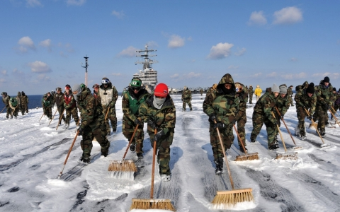 Sailors scrub the external surfaces on the flight deck of the USS Ronald Reagan to remove potential radiation contamination on March 23, 2011.