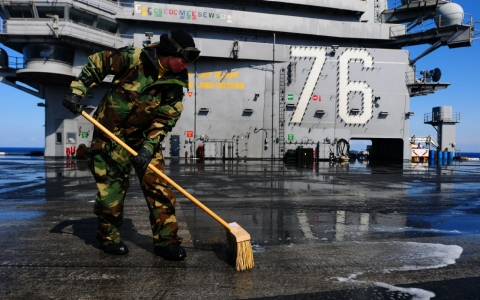 Aviation Boatswain's Mate, 3rd Class Ashton Hemphill, scrubs the flight deck of the USS Ronald Reagan on March 23, 2011 at sea in the Pacific Ocean.
