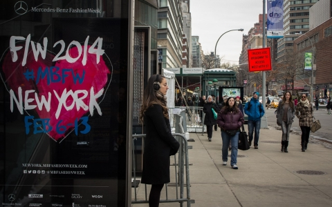 A woman stands near a New York Fashion Week poster at Lincoln Center on Feb. 9, 2014.