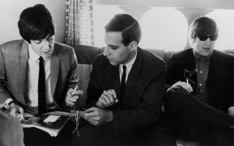 From left to right, Paul McCartney, Larry Kane, and John Lennon aboard a plane circa 1964.