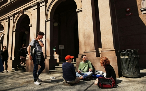 Students sit in front of Cooper Union for the Advancement of Science and Art