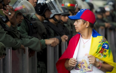 Woman walks past Bolivarian National Guard during protests.