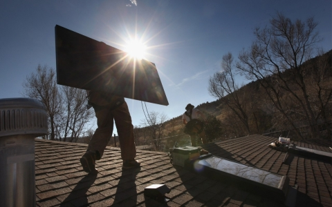 Men install solar panel on roof of house.