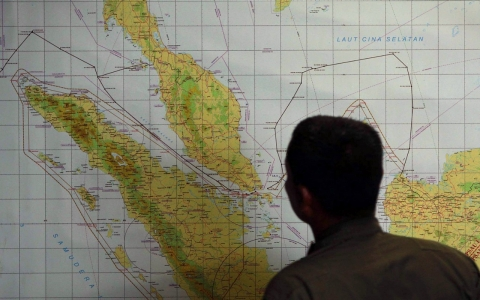 A member of the Indonesian Air Force inspects the Indonesian military search operation for the missing Malaysia Airlines flight MH370.