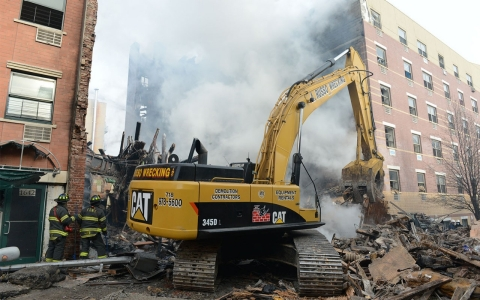 Workers search through debris in the smoking site of an explosion in East Harlem on March 13, 2014 in New York City.
