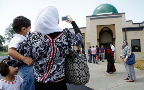 A woman takes a picture of the Islamic Center of Murfreesboro after midday prayers.