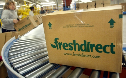 Workers prepare boxes of groceries at a FreshDirect warehouse.